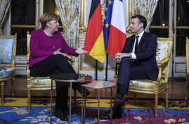 France's President Emmanuel Macron, right, and German Chancellor Angela Merkel, talk during their meeting, at the Elysee Palace, in Paris, Jan. 19, 2018.