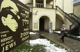 FILE - A tourist walks out from the Izaak Synagogue in the Krakow district of Kazimierz, Poland, once a Jewish part of the town.