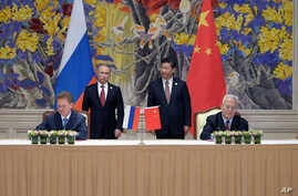 Russia's President Vladimir Putin (Background L) and China's President Xi Jinping (Background R) watch during a signing ceremony in Shanghai, China, May 21, 2014, as Russian Gazprom CEO Alexei Miller, Foreground L) and China's CNPC head Zhou Jiping (