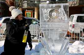 Ice sculptor Deneena Hughes applies the finishing touches with a blow torch to the VOA logo. (Brian Allen/VOA)