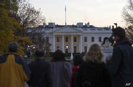 People gather outside the White House in Washington after the Secret Service arrested a man who was caught jumping the fence as President Barack Obama and his family ate Thanksgiving dinner, Nov. 26, 2015.