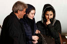 Italian aid workers, 21-year-old Greta Ramelli, center, and 20-year-old Vanessa Marzullo, right, are welcomed by Foreign Minister Paolo Gentiloni as they arrive at Ciampino's military airport, near Rome, early Friday, Jan. 16, 2015.