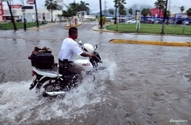 A man drives his motorcycle through a street flooded by rain brought by Hurricane Raymond in Acapulco, Oct. 21, 2013.
