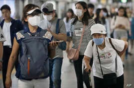 Passengers wearing masks as a precaution against the MERS virus make their way after they got off a train at a subway station in Seoul, South Korea, June 18, 2015.