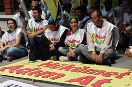 Kurds sit next to a banner that reads 'government, take steps' after Kurdish rebels gave Turkey a 'final warning' to take steps that would move forward peace talks aimed at ending a 30-year old conflict that has claimed tens of thousands of lives, in
