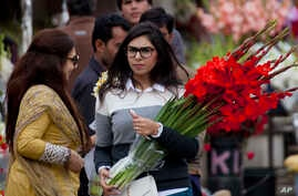 People buy flowers at a flower market, to celebrate Valentine's Day, in Islamabad, Pakistan, Tuesday, Feb. 14, 2017.