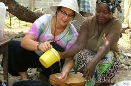 Sara Laskowski , left, gets a cooking lesson from her Peace Corps 'host mother' in Dubreka, Guinea. Since shortly after the Peace Corps pulled volunteers from Ebola-afflicted countries, the young American has promoted an Ebola aid fund for the Nation