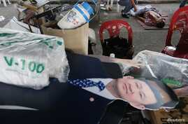 Cut-out image of former prime minister Thaksin Shinawatra near body of a man killed near stadium where pro-government red shirts gathered, Bangkok, Dec. 1, 2013.