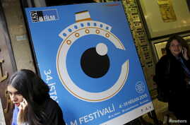 People speak on their mobile phones next to a banner of Istanbul Film Festival at the entrance of Atlas movie theatre in Istanbul April 14, 2015. Nearly two dozen filmmakers and a group of international critics pulled out of the festival after the go