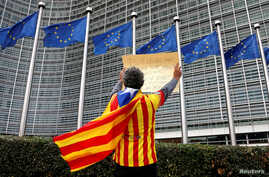 Catalan Raimon Castellvi wears a flag with an Estelada (Catalan separatist flag) as he protests outside the European Commission in Brussels after Sunday's independence referendum in Catalonia, Belgium, Oct. 2, 2017.