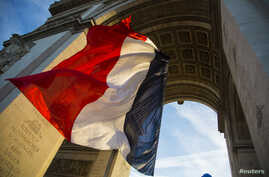 FILE - The French flag flies under the Arc de Triomphe during a ceremony to commemorate the end of the World War One in Paris, Nov. 11, 2013.