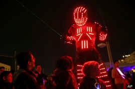 Young participants look at a performer wearing a luminous costume entertaining a crowd in Lisbon, Portugal, during the symbolic switching off of the lights known as Earth Hour, March 28, 2015.