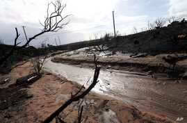 Mud and debris has flowed down normally dry Solstice Creek in an area burned by the Woolsey Fire in Malibu, Calif.,  Nov. 29, 2018.