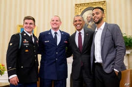 President Barack Obama poses for a photograph with Oregon National Guardsman, from left, Alek Skarlatos, Air Force Airman 1st Class Spencer Stone, and Anthony Sadler, in the Oval Office of the White House in Washington, Thursday, Sept. 17, 2015.