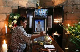 A woman dips a flower in a glass of water placed on the coffin of slain journalist Gumaro Perez during his wake inside his mother's home in Acayucan, Veracruz state, Mexico, Wednesday, Dec. 20, 2017.