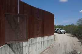 FILE - A U.S. Customs and Border Patrol vehicle passes along a section of border wall in Hidalgo, Texas, between the U.S. and Mexico, Aug. 11, 2017.