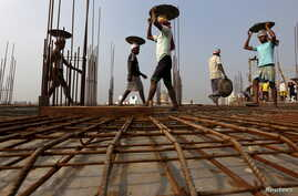 FILE - Laborers work at the construction site of a residential complex on the outskirts of Kolkata, India, Jan. 23, 2016.