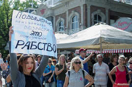 "People attend a rally against planned increases to the nationwide pension age in Krasnodar, Russia, Sept. 9, 2018. The poster reads: ""Pension age increase is a lifetime slavery."""