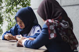 FILE - Women use their smart phones at a cafe in Jakarta, Jan. 3, 2018.