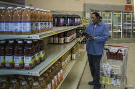 Joseph Miller selects a bottle of fruit juice available through the U.S. Department of Agriculture (USDA) Food Distribution Program on Indian Reservations (FDIPR) at the Acoma Food Distribution Program Warehouse in the Pueblo of Acoma, NM.  USDA phot