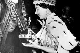 In this June 2, 1953 file photo, Britain's Queen Elizabeth II wearing the bejeweled Imperial Crown and carrying the Orb and Scepter with Cross, leaves Westminster Abbey, London, at the end of her coronation ceremony
