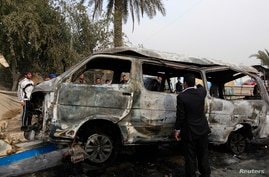 FILE - A man inspects a damaged vehicle at the site of a bomb attack in Baghdad Feb. 16, 2014.