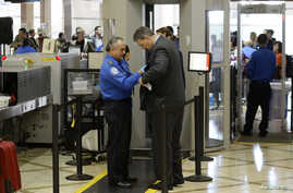 FILE An airline passenger is patted down by a TSA agent after passing through a full-body scanner at Los Angeles International Airport in Los Angeles, California, Feb. 20, 2014. The TSA is under renewed scrutiny as waiting periods for passenger scree...