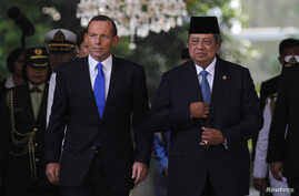 Australian Prime Minister Tony Abbott (L) walks beside Indonesian President Susilo Bambang Yudhoyono at the Presidential Palace in Jakarta, September 30, 2013. Abbott, accompanied by the Minister for Foreign Affairs Julie Bishop, Minister for Trade a