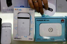 vA worker takes a Huawei mobile Internet device next to it competitor ZTE Corp, left, which are displayed for sale at a computer mall in Beijing Wednesday, July 4, 2018.