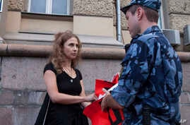 Russian activist of the feminist protest group Pussy Riot Maria Alekhina talks to a policeman as she holds a protest in front of the Federal Penitentiary building in Moscow, Russia, Aug. 7, 2018.