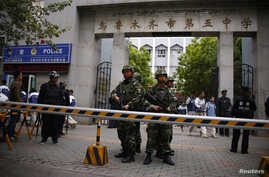 FILE - Paramilitary policemen stand guard in front of Urumqi No. 5 middle school after Thursday's attack in downtown Urumqi, Xinjiang, Uighur Autonomous Region.