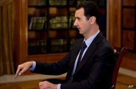 In this photo, which AP obtained from Syrian official news agency SANA and which has been authenticated based on its contents and other AP reporting, President Bashar Assad gestures as he speaks during an interview with Lebanon's Al-Mayadeen TV, at t