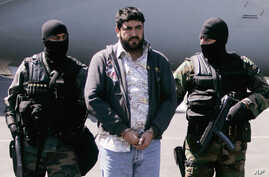 "FILE - In this Jan. 21, 2008 photo, Mexican federal police officers escort Alfredo Beltran Leyva, known as ""El Mochomo"", after his arrest upon his arrival to Mexico City's airport."