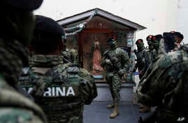 A soldiers poses for a photo with a statue of the Virgin of Guadalupe before the start of the annual Independence Day military parade in Mexico City's main square, known as the Zocalo, Sept. 16, 2017. Mexico is considering a law to give the military