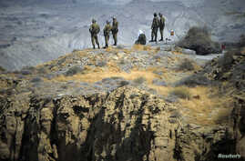FILE - Members of Iran's Revolutionary guard monitor an area as they stand on a hill top in the Hormuz area of southern Iran, April 24, 2010.