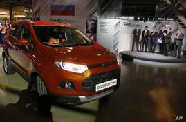 FILE - Russian Prime Minister Dmitry Medvedev, second right, attends the launch of Ford EcoSport production during a visit to Ford Sollers at a plant in Naberezhnye Chelny, about 700 kilometers (450 miles) east of Moscow, Dec. 2, 2014.
