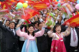 North Koreans wave flower bouquets and balloons as they march during a parade at the Kim Il Sung Square on Tuesday, May 10, 2016.