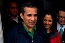 FILE- Peru's former President Ollanta Humala and his wife, Nadine Heredia, talk with journalists as they leave the headquarters of Peru's National Party in Lima, Peru, July 13, 2017.