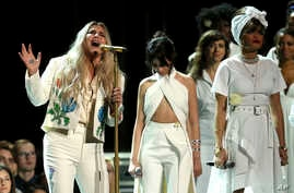 """Kesha, left, performs """"Praying"""" as Camila Cabello, center, and Andra Day stand by at the 60th annual Grammy Awards at Madison Square Garden on Sunday, Jan. 28, 2018, in New York."""