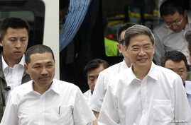 Zhang Zhijun (R), director of China's Taiwan Affairs Office, arrives with New Taipei City Deputy Mayor Hou You-yi, at the labour activity centre in New Taipei City, June 26, 2014.