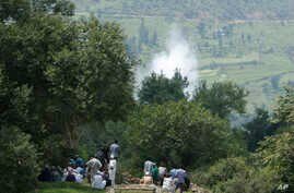 Smoke rises behind from a mortar shell fired by Pakistani troops as Indian villagers sit during the funeral of Indian civilian Sarpanch Karamat Hussain who was killed in Pakistani shelling at Balakot sector in Poonch, Jammu and Kashmir, India, Aug.16