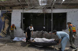 Pakistani volunteers and rescue workers remove a lifeless body from the site after a bomb explosion in Peshawar, Pakistan, May 11, 2014.