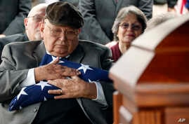 Frank Springs, of Lucedale, hugs the American flag that draped the casket of his uncle, Navy Fireman 1st Class Jim H. Johnston, who was buried, Dec. 7, 2016, with full military honors in Wesson, Miss., his hometown.