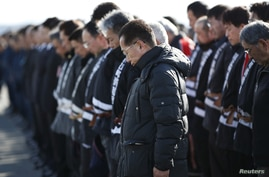 Police officers and firefighters observe a moment of silence at 2:46 p.m. (0546 GMT), the time when the magnitude 9.0 earthquake struck off Japan's coast in 2011, in Namie town, Fukushima prefecture, March 11, 2014.
