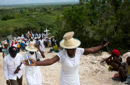 A woman stretches out her arms in prayer as she balances a stone on her head as a form of penance during a Good Friday ritual, in Ganthier, Haiti, April 14, 2017.