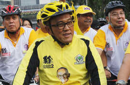 FILE - Aburizal Bakrie cycling with his party members in Jakarta, Oct. 21, 2012.