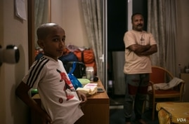 Syed Nadim Rizwi is seen in his room with one of his sons. A Shia Muslim, he fled Pakistan after a number of relatives were murdered. (J. Owens/VOA)