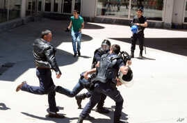 Turkish riot police try to protect a person from a group of people of unknown affiliation who were attacking a rally of pro-Kurdish Peoples' Democracy Party, (HDP) in eastern city of Erzurum, Turkey, Thursday, June 4, 2015.