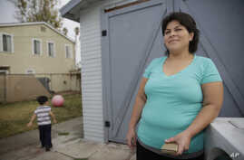 FILE - Central American refugee Roxana Janet Castillo poses for a photo at her home in Los Angeles, Dec. 10, 2015. Castillo applied for the Central American Minors (CAM) Refugee/Parole Program to bring her three children legally from her native El Sa