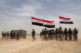 U.S. soldiers, left, participate in a training mission with Iraqi army soldiers outside Baghdad, Iraq, Wednesday, May 27, 2015. Islamic State extremists unleashed a wave of suicide attacks targeting the Iraqi army in western Anbar province, killing a...